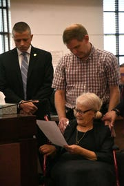 Josey Visnovske, a family friend of the Williams family, left, Nick Williams, brother of Mike Williams the man who was murdered 18 years ago by his best friend and wife, stand with Cheryl Williams, Mike Williams mother, as she reads her victim impact statement to the courtroom during the sentencing for Mike's wife, Denise Williams, Wednesday Feb. 6, 2019. Williams was sentenced to life in prison plus 30 years.