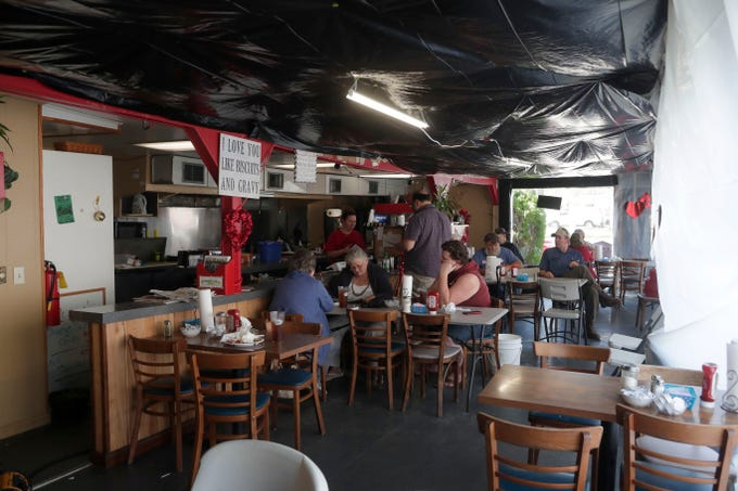 The inside of the Waffle Iron in Marianna, Fla. is bustling with people coming in for lunch despite the tarps covering the windows and ceiling, Tuesday Feb. 5, 2019. Hurricane Michael tore apart the Waffle Iron in Oct. 2018.