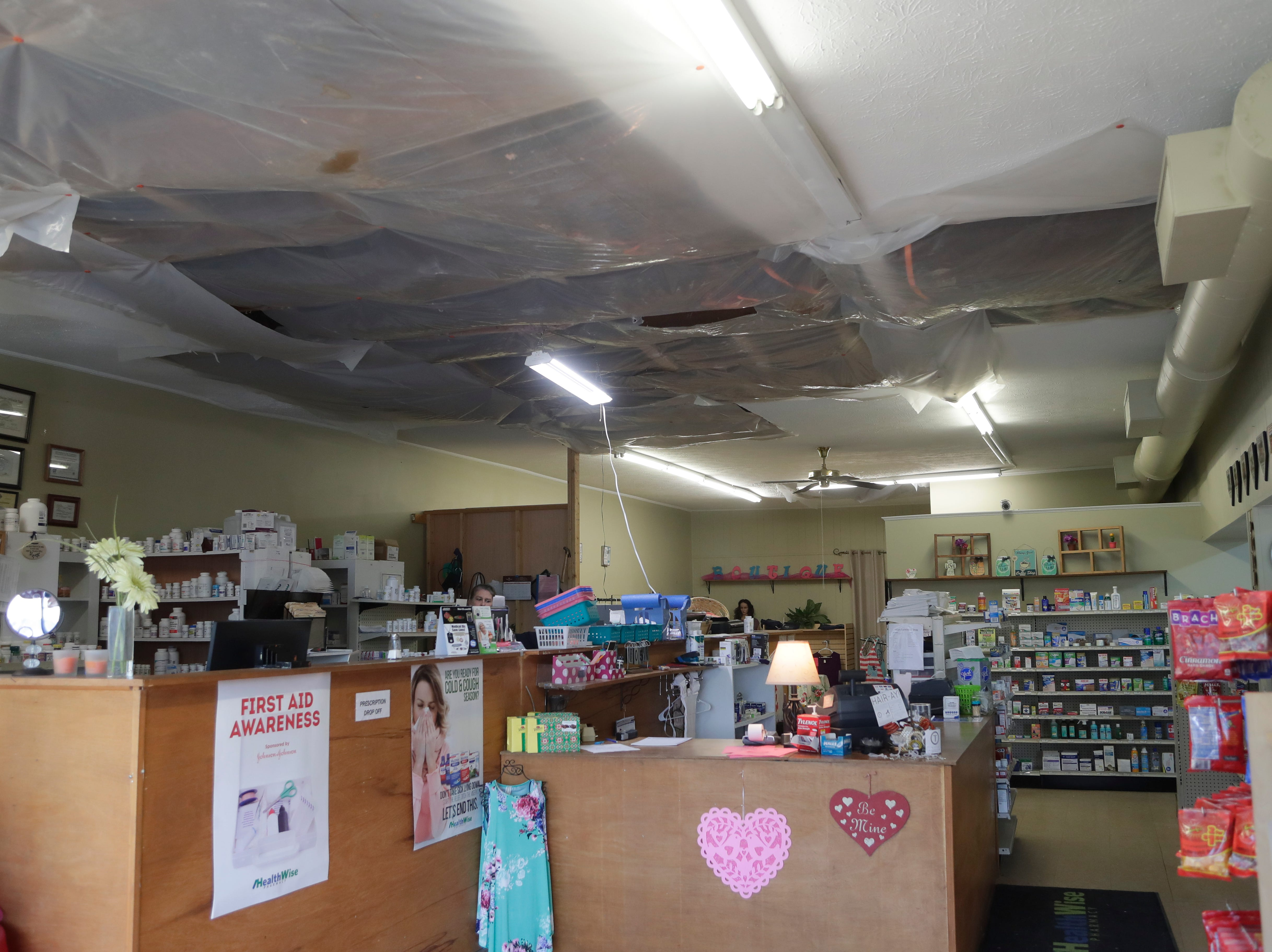 The ceiling of Yates Pharmacy and Gifts has tarp covering the openings created four months prior by Hurricane Michael.