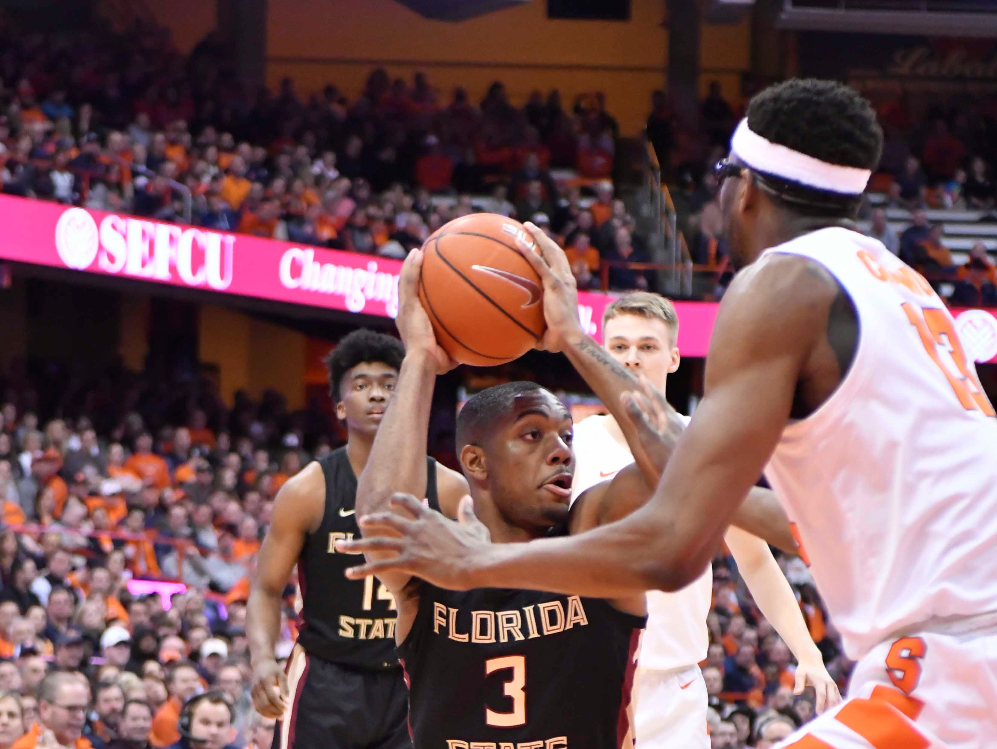 Feb 5, 2019; Syracuse, NY, USA; Florida State Seminoles guard Trent Forrest (3) looks to make a move with the ball as Syracuse Orange center Paschal Chukwu (13) defends in the first half at the Carrier Dome. Mandatory Credit: Mark Konezny-USA TODAY Sports