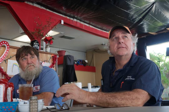 Waffle Iron customers Rusty Lawrence, left, and Neil Glover, right, place their lunch orders with Ashley Hendrix, a server at the Waffle Iron in Marianna, Fla., Tuesday Feb. 5, 2019. The Waffle Iron was badly damaged by Hurricane Michael in Oct. 2018, and is still in need of a new roof.