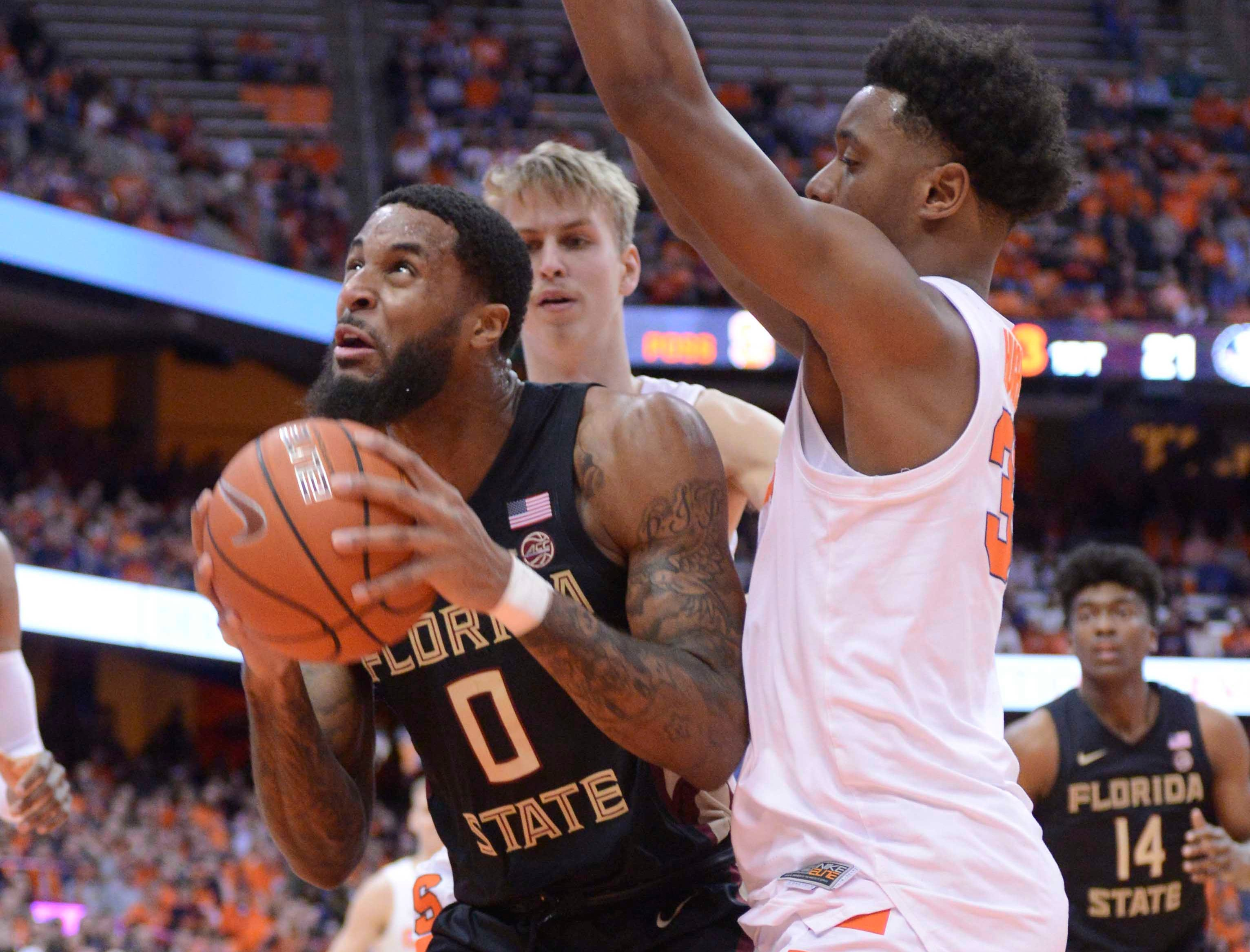 Feb 5, 2019; Syracuse, NY, USA; Florida State Seminoles forward Phil Cofer (0) looks to take a shot as Syracuse Orange forward Elijah Hughes (right) defends in the first half at the Carrier Dome. Mandatory Credit: Mark Konezny-USA TODAY Sports