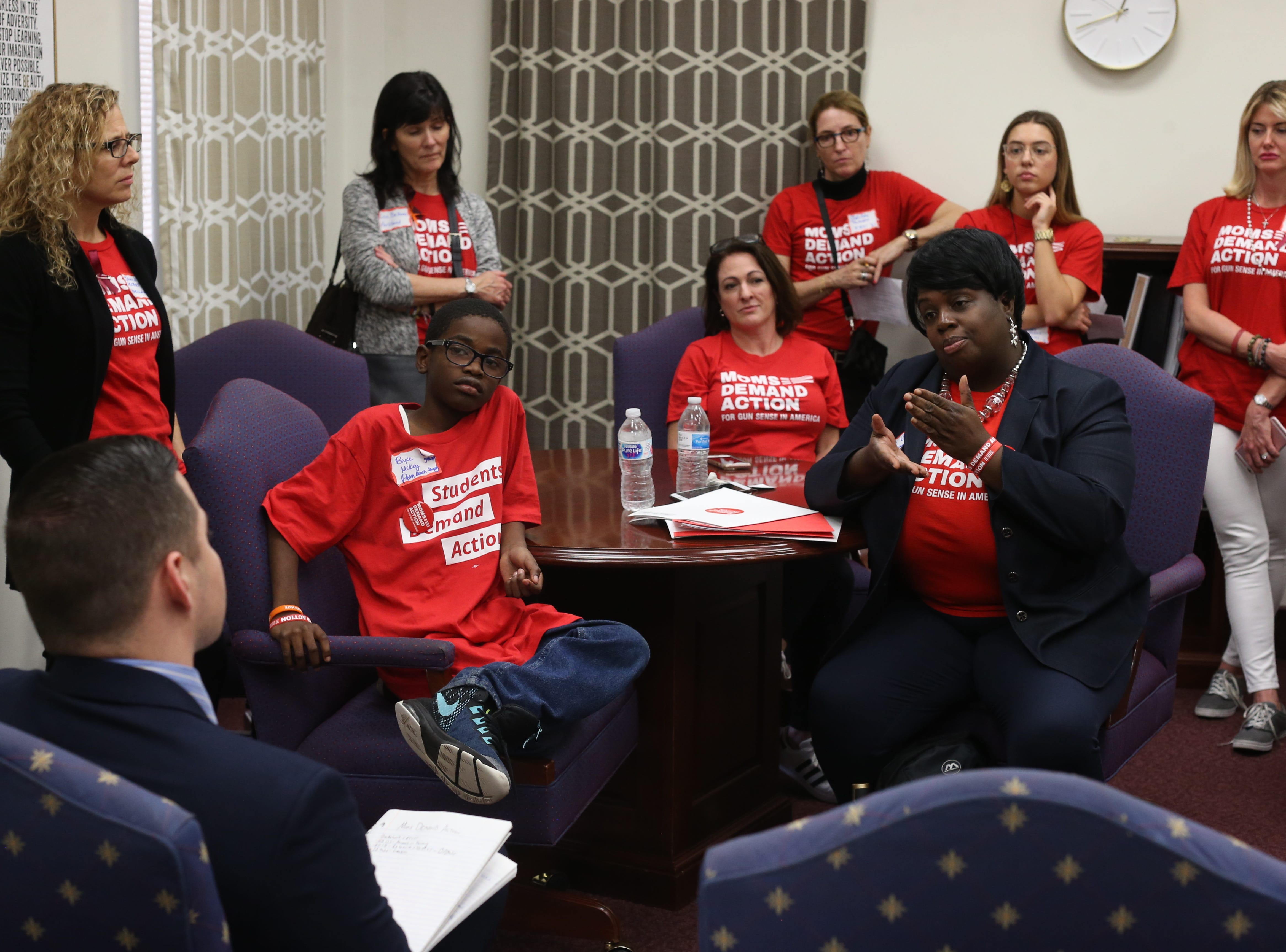 Teisha Mckoy, a member of Moms Demand Action from Palm Beach County, talks to Tomas Alcala, a legislative assistant to Sen. Bobby Powell in Powell's office Wednesday, Feb. 6, 2019. Mckoy and over 500 members of Moms Demand Action visited lawmakers at the Capitol to lobby for stricter gun laws.