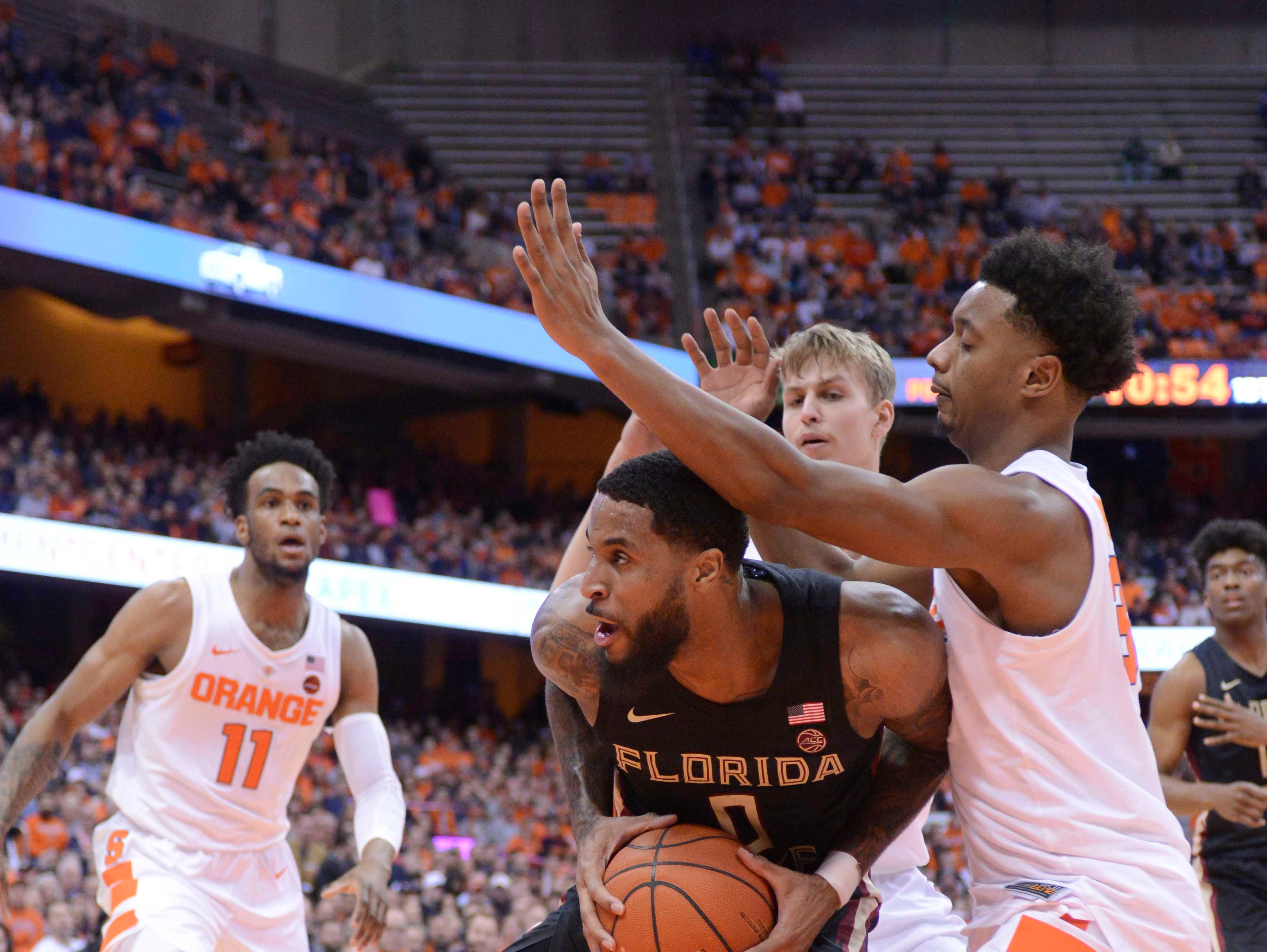 Feb 5, 2019; Syracuse, NY, USA; Florida State Seminoles forward Phil Cofer (0) grabs a rebound as Syracuse Orange forward Elijah Hughes (right) defends in the first half at the Carrier Dome. Mandatory Credit: Mark Konezny-USA TODAY Sports