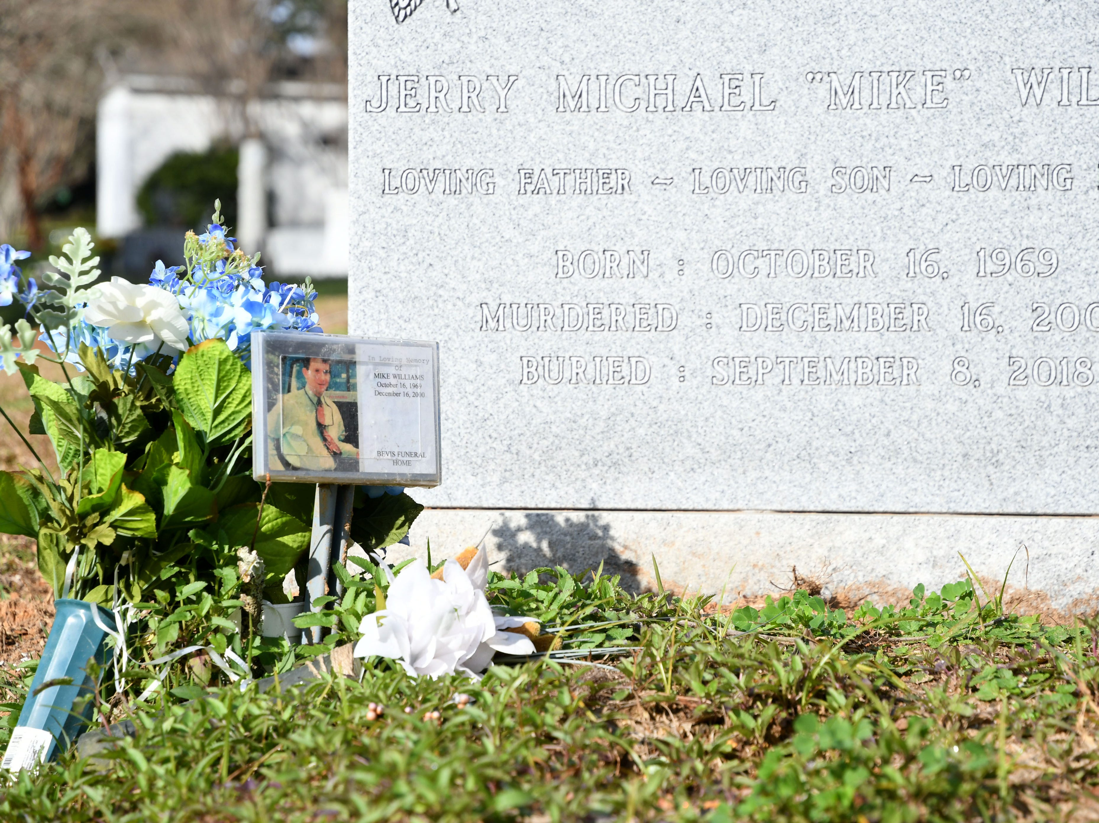 A small bouquet of flowers a photo of Mike Williams sit next to his tombstone. Williams is the man who was murdered over 18 years ago by his wife and best friend. Denise Williams, Mike's wife, was sentenced to life in prison plus 30 years, Wednesday Feb. 6, 2019.