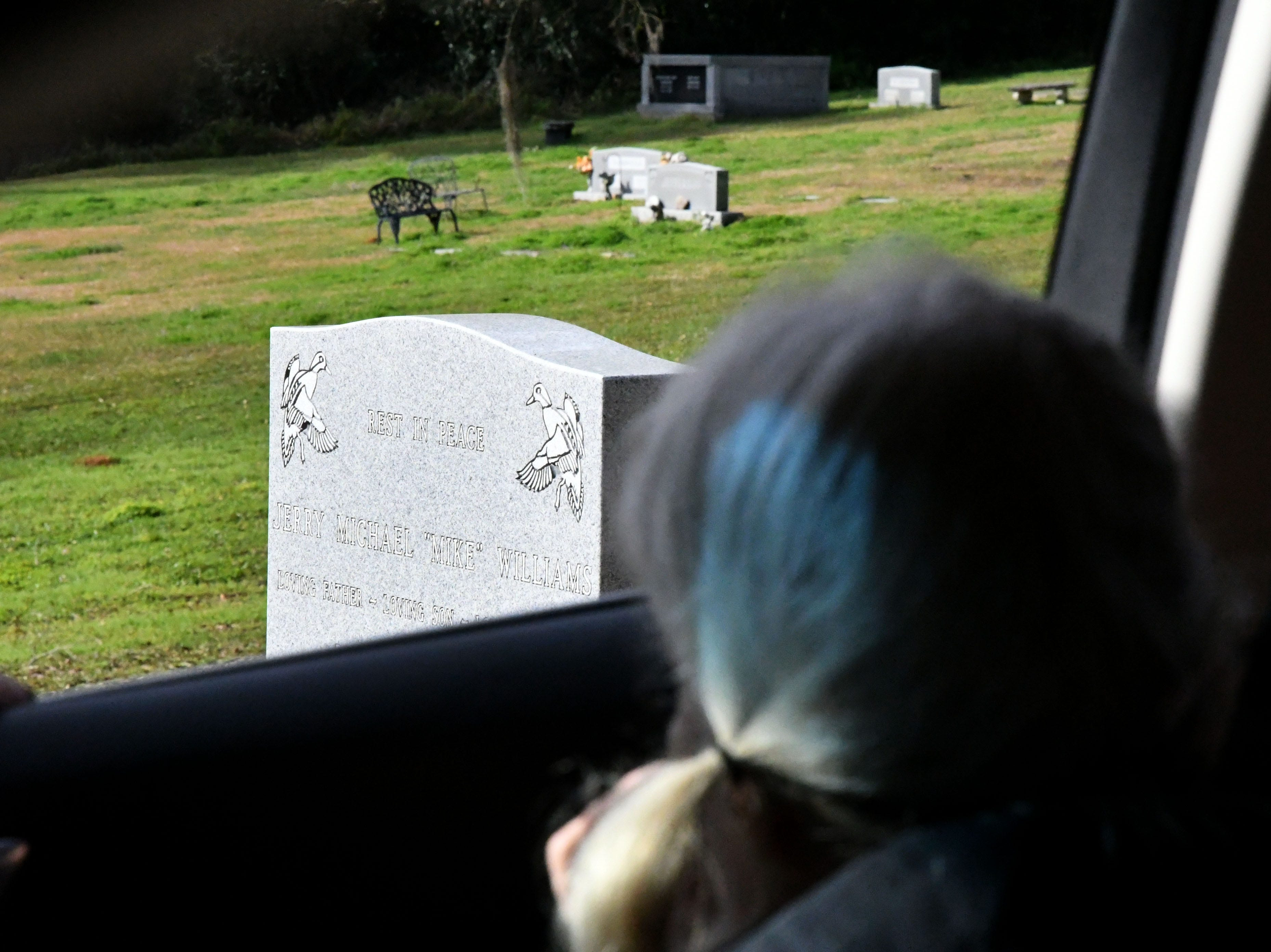 Cheryl Williams, mother of Mike Williams, the man who was murdered over 18 years ago, looks out from the passenger side car window at her son's tombstone, Wednesday Feb. 6, 2019.