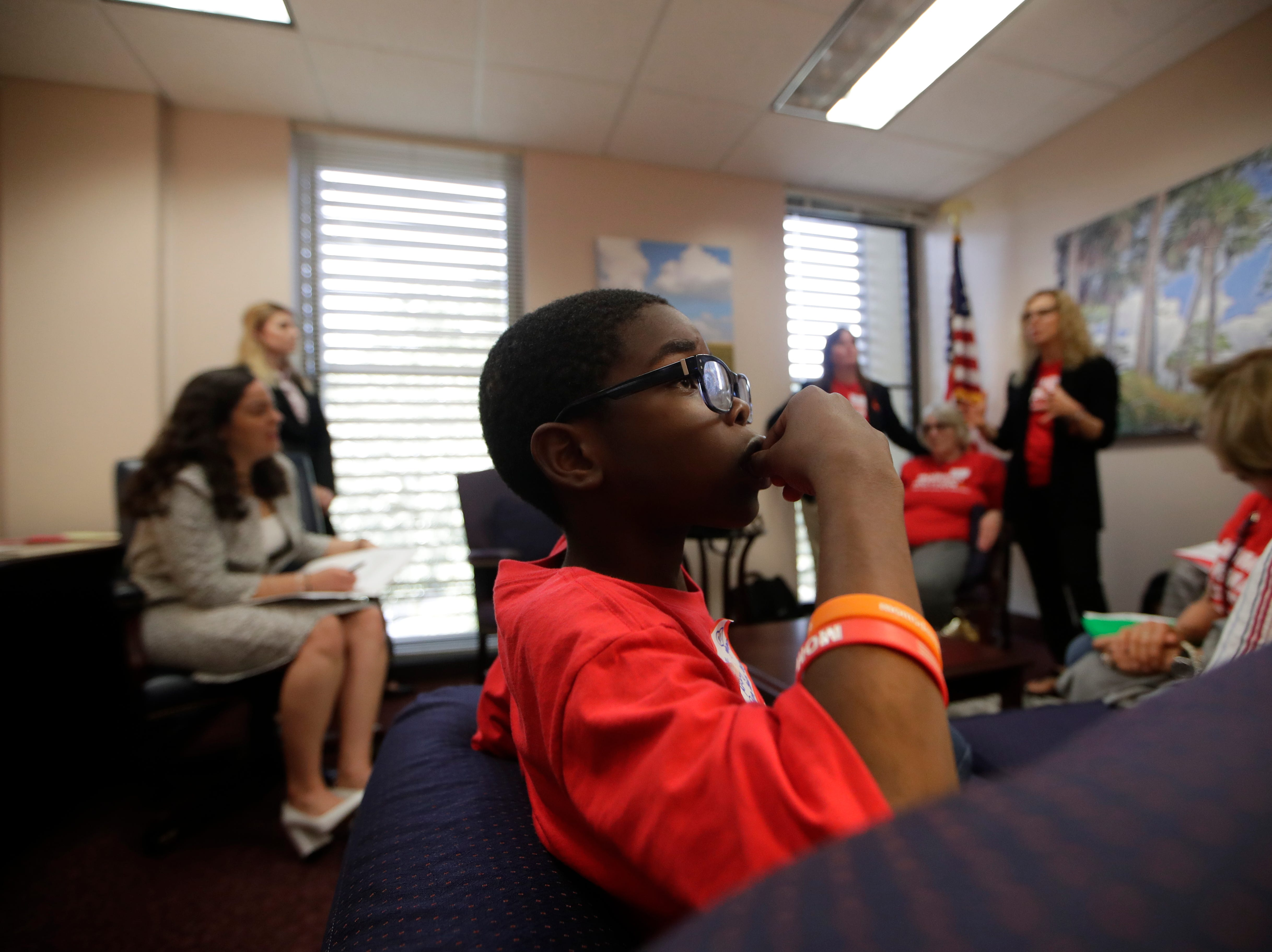 Bryce Mckoy, 9, sucks on a Jolly Rancher while his mother Teisha Mckoy and a group from Mothers Demand Action speak to Karina Pereira, a legislative assistant to Rep. Kirstin Jacobs in her office at the Capitol Wednesday, Feb. 6, 2019. Over 500 members of Moms Demand Action from across Florida met with lawmakers at the Capitol to lobby for stricter gun laws.