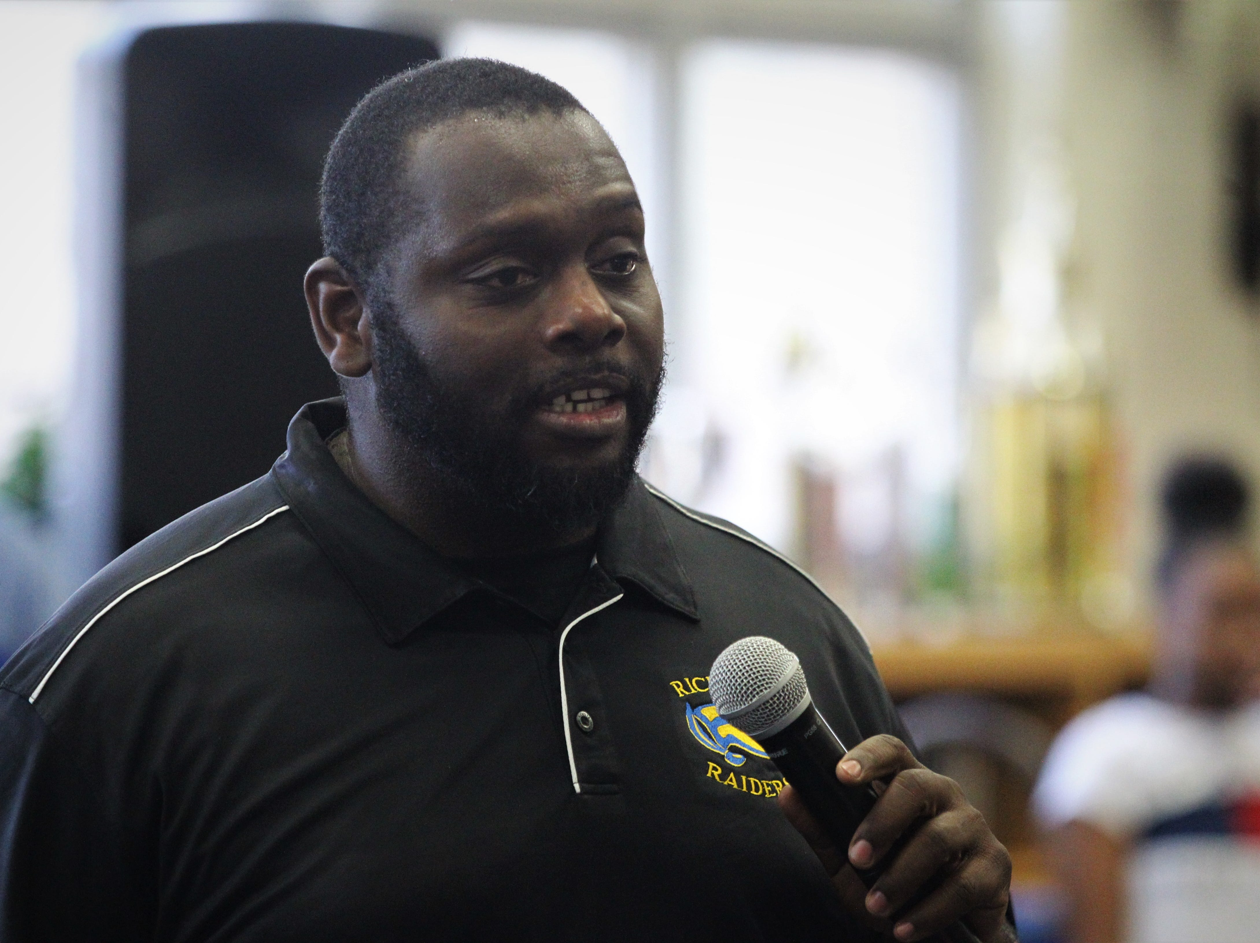 Rickards football coach Quintin Lewis talks during signing ceremonies on National Signing Day, Feb. 6, 2019.