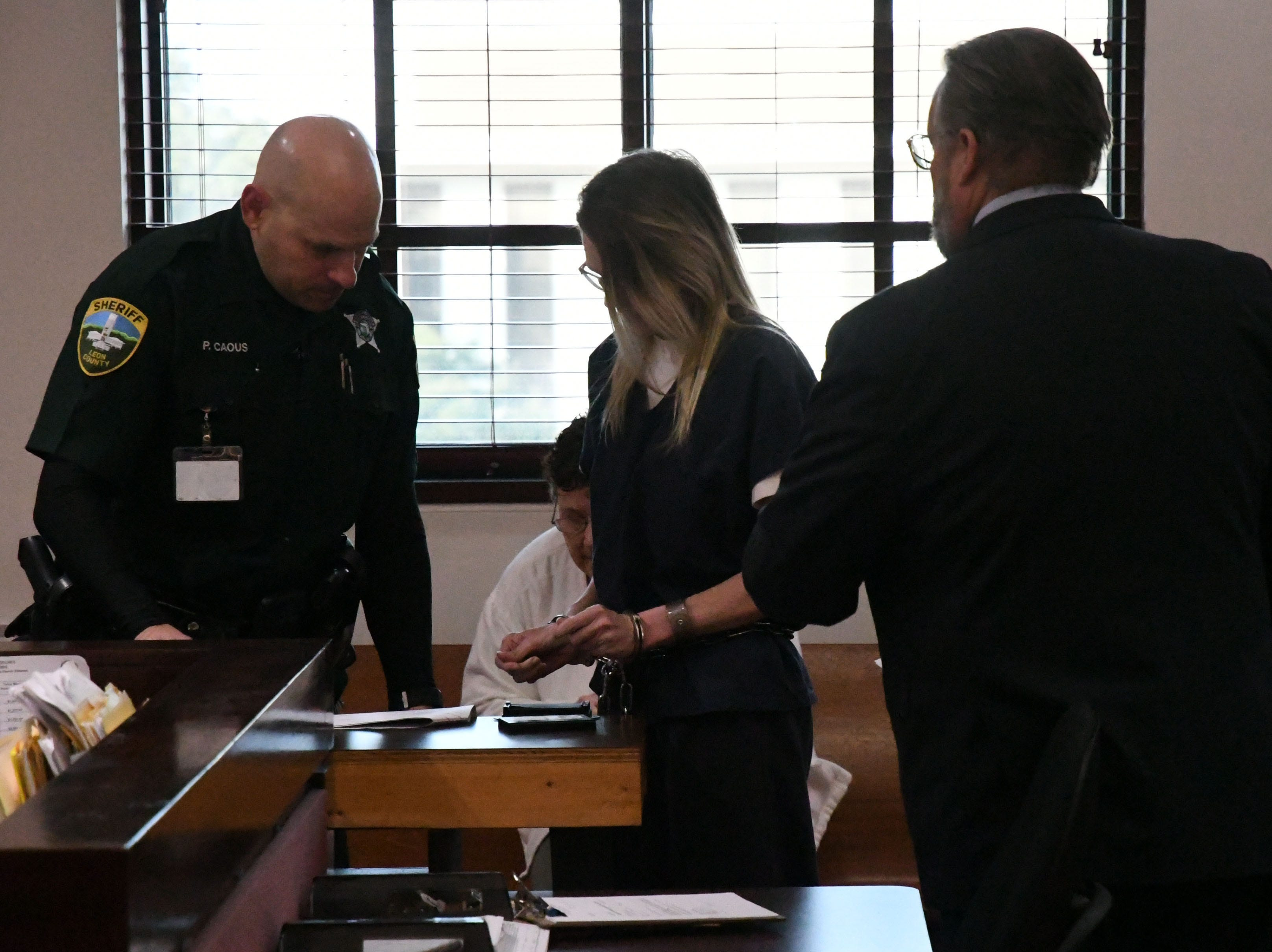 Denise Williams has her finger prints done by the bailiff before her sentencing, Wednesday Feb. 6, 2019, for the murder of her husband, Mike Williams. Williams was sentenced to life in prison plus thirty years.