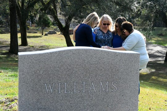 Mary Denmark, left, Amber Brogdon Page, Shari Javorsky, Mary Christy Denmark, and Denise Brogdon, all family friends of the Williams' family, pray together at the Mike Williams' final resting place, Wednesday Feb. 6, 2019. Williams was murdered over 18 years ago by his wife and best friend. Denise Williams, Mike's wife, was sentenced to life in prison plus 30 years.