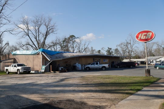The IGA in Malone, Fla. is open for business despite having a blue tarp covering the roof and boarded up windows, Tuesday Feb. 5, 2019. Hurricane Michael ripped off a portion of the roof and blew out the windows of the grocery store in Oct. 2018.