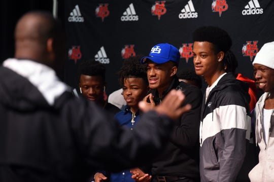Vero Beach High School football player Javien Cuff (center) stands with friends and fellow teammates for a photo on Wednesday, Feb. 6, 2019, during a National Signing Day ceremony at the Performing Arts Center at Vero Beach High School. Cuff signed a letter to play football for the University at Buffalo. Six other Vero Beach student athletes also signed letters to play at the college level.
