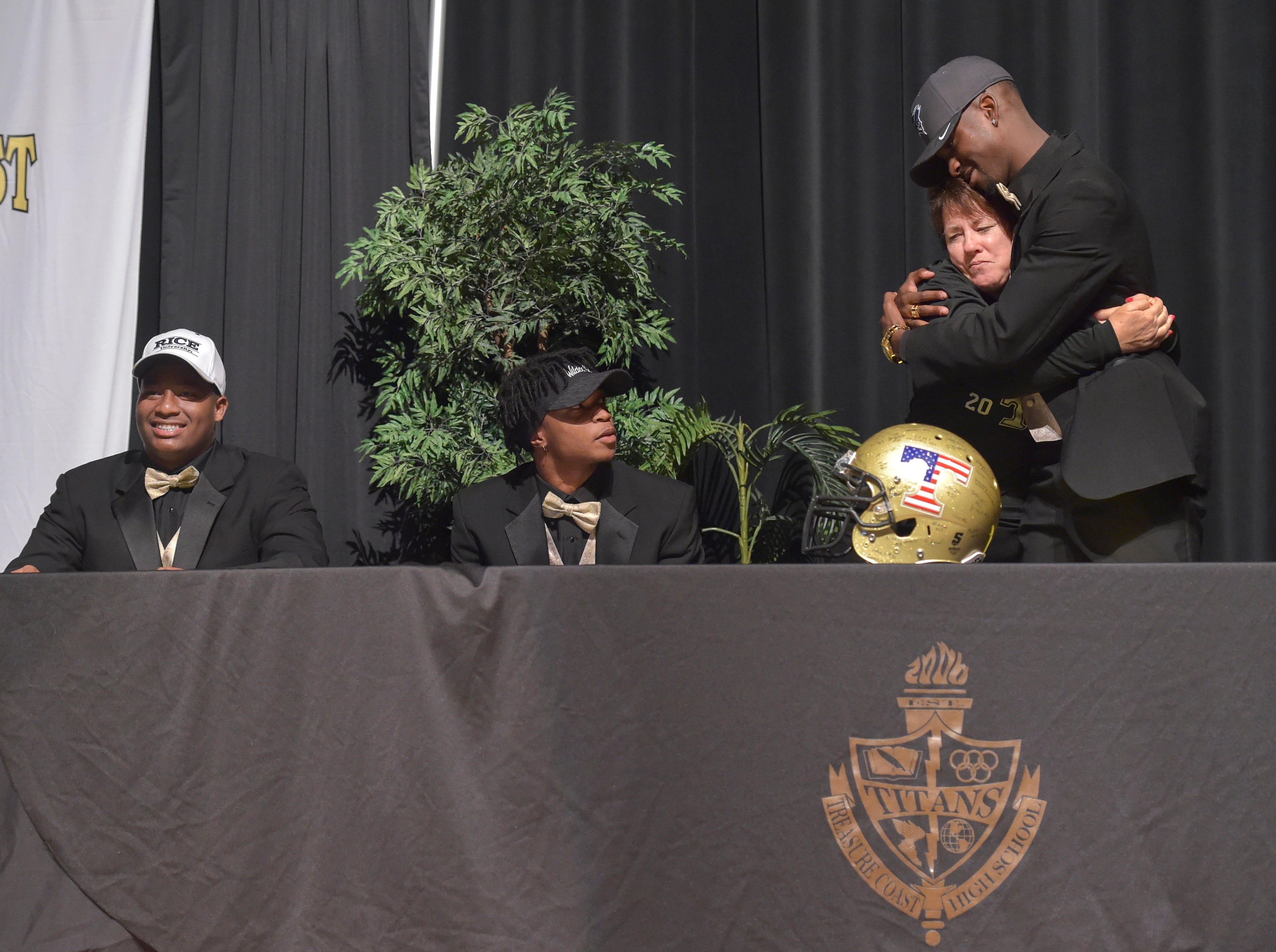 "Treasure Coast High School Principal Susan Seal (third from left) shares a hug with Tyrec Thompson while with (from left) Jerry Johnson and Shamar Minnis during the school's National Signing Day ceremony for football and baseball athletes on Wednesday, Feb. 6, 2019, inside the school's auditorium.  ""Great kids,"" Seal said. ""It feels wonderful because they came here my first year as a principal, so it's really neat to watch the evolution of young men who are not sure where they're headed, and being faced with a lot of obstacles and different choices, to be able to, for them, to see that success is just amazing."" Thompson signed with Iowa Western, Johnson signed with Rice University, and Minnis signed with Bethune-Cookman, all to play football. ""It feels amazing,"" Thompson said. ""I'm happy for my family, friends, and coaching staff, and the people that helped me get to where I am today."""