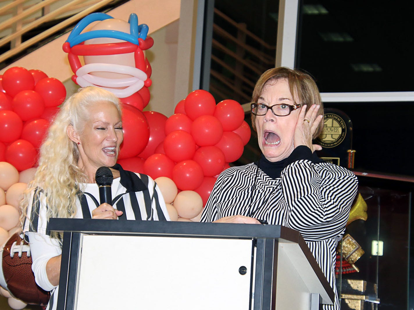 Voices for Children volunteer Kip Lyman, left, and Fort Pierce Mayor Linda Hudson react to the event's opening whistle at the Ultimate Tailgate Party on Jan. 26 at Treasure Coast Lexus.