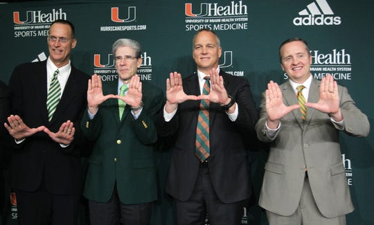 (From left) University of Miami radio voice Don Bailey; university president Julio Frenk; Mark Richt; and athletic director Blake James gesture Dec. 4, 2015, after a press conference where Richt was introduced as the new NCAA college football head coach at the University of Miami in Coral Gables.