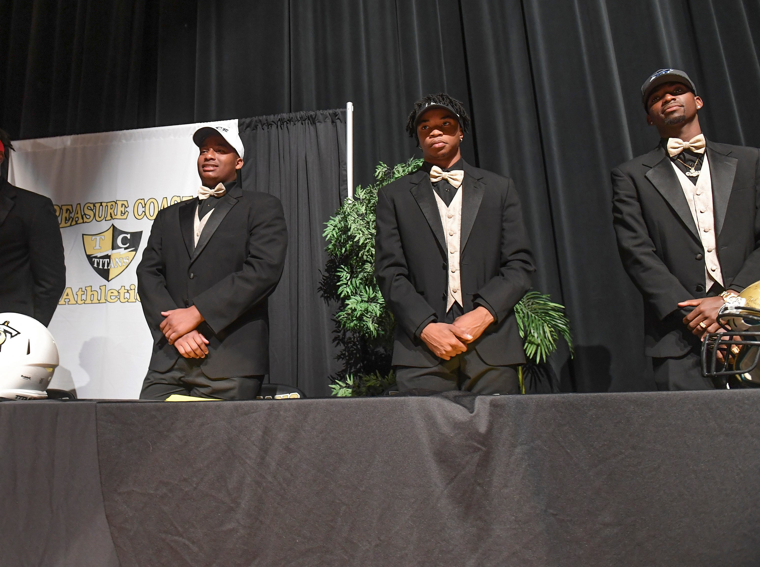 Treasure Coast High School football players (from left) Joel Rose, Jerry Johnson, Shamar Minnis, and Tyrec Thompson, are seen at the start of the school's National Signing Day celebration, where the athletes announce their college choices during the ceremony on Wednesday, Feb. 6, 2019, inside Treasure Coast High School's auditorium. Rose signed with Valdosta State, Johnson signed with Rice University, Minnis signed with Bethune-Cookman University, Thompson signed with Iowa Western, and (not pictured) Joshua Nunes signed with Central State University in Ohio, Brendon Joseph signed with Ave Maria University, and Anthony Martens signed with University of West Florida to play baseball.