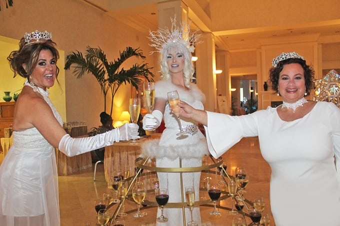 Ice Princesses Cindy Goetz, left, and Liz Mayo, right, toast Snow Queen Anna as she offers champagne and wine to the guests at the Gifford Youth Achievement Center's Snow Ball at Oak Harbor.