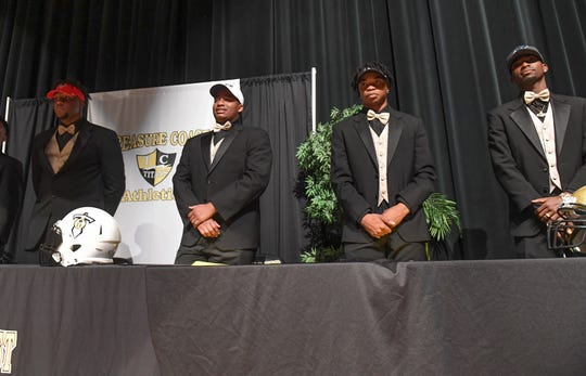 Treasure Coast High School football players (from left) Joel Rose, Jerry Johnson, Shamar Minnis, and Tyrec Thompson, are seen at the start of the school's National Signing Day celebration, where the athletes announce their college choices on Wednesday, Feb. 6, 2019, inside Treasure Coast High School's auditorium in Port St. Lucie. Rose signed with Valdosta State, Johnson signed with Rice University, Minnis signed with Bethune-Cookman University, Thompson signed with Iowa Western, and (not pictured) Joshua Nunes signed with Central State University in Ohio, Brendon Joseph signed with Ave Maria University, and Anthony Martens signed with University of West Florida to play baseball.