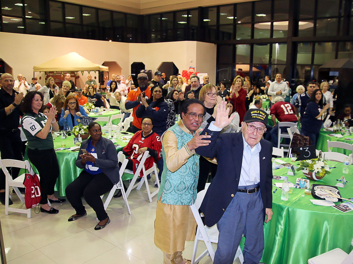 Dr. Shamsher Singh helps 100-year-old World War II Veteran Pete Peterson to his feet for an extended standing ovation at the Voices for Children Ultimate Tailgate Party on Jan. 26 at Treasure Coast Lexus.