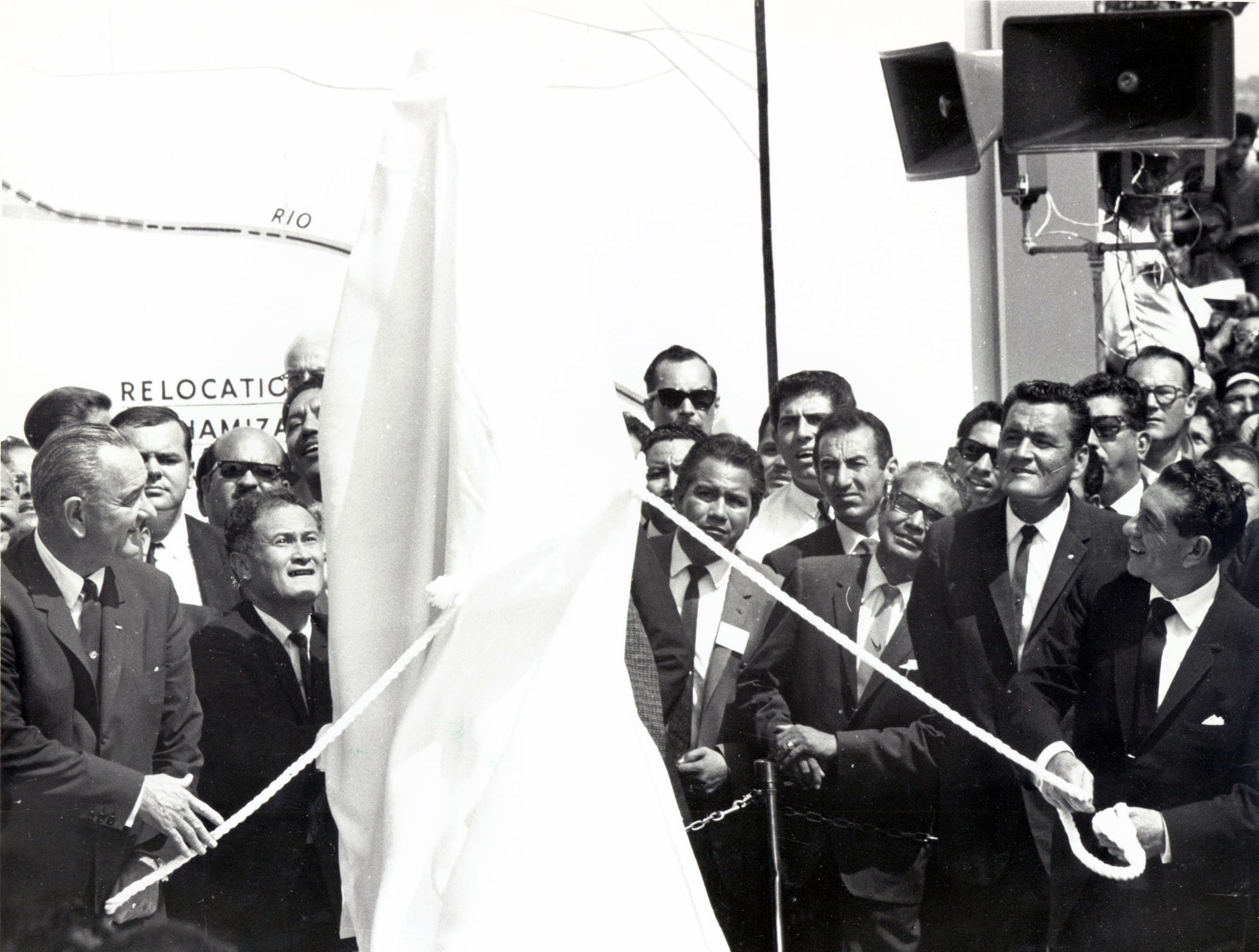 September 25, 1964 - UNVEIL MARKER -- President Lyndon Johnson, left, and Lopez Mateos, right prepare to unveil the shining chrome monument marking the new boundary of Mexico and the United States near Bowie High School. Following the ceremony, the Presidents were given two framed artistic renderings symbolizing settlement of the Chamizal. The drawings, which appeared in The Times Friday, were prepared by Artist Bob Kolliker.