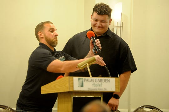 Pacifica High head coach Mike Moon fixes the microphone height for offensive lineman Armando Sifuentes during the Ventura County coaches' annual signing day banquet at the Palm Garden Hotel in Newbury Park on Wednesday. Sifuentes will play at Azusa Pacific University.
