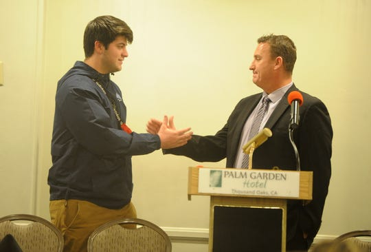 Westlake High's Stone Martin shakes hands with head coach Tim Kirksey  during the Ventura County coaches' annual signing day banquet at the Palm Garden Hotel in Newbury Park on Wednesday. Martin will attend the University of San Diego.