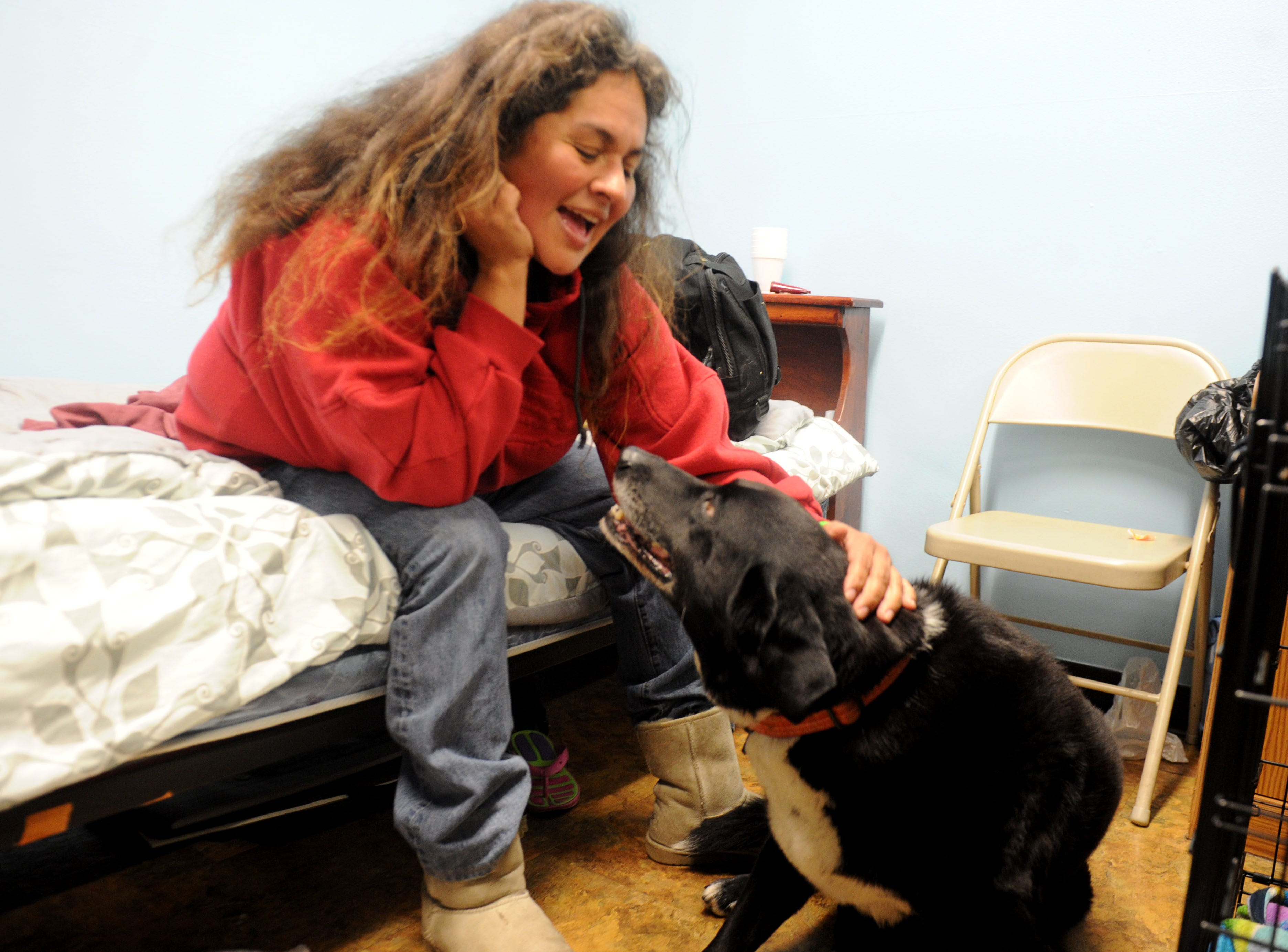 Noe Estrella pets her dog Malu at the Oxnard homeless shelter, which now allows guests to bring their pets.