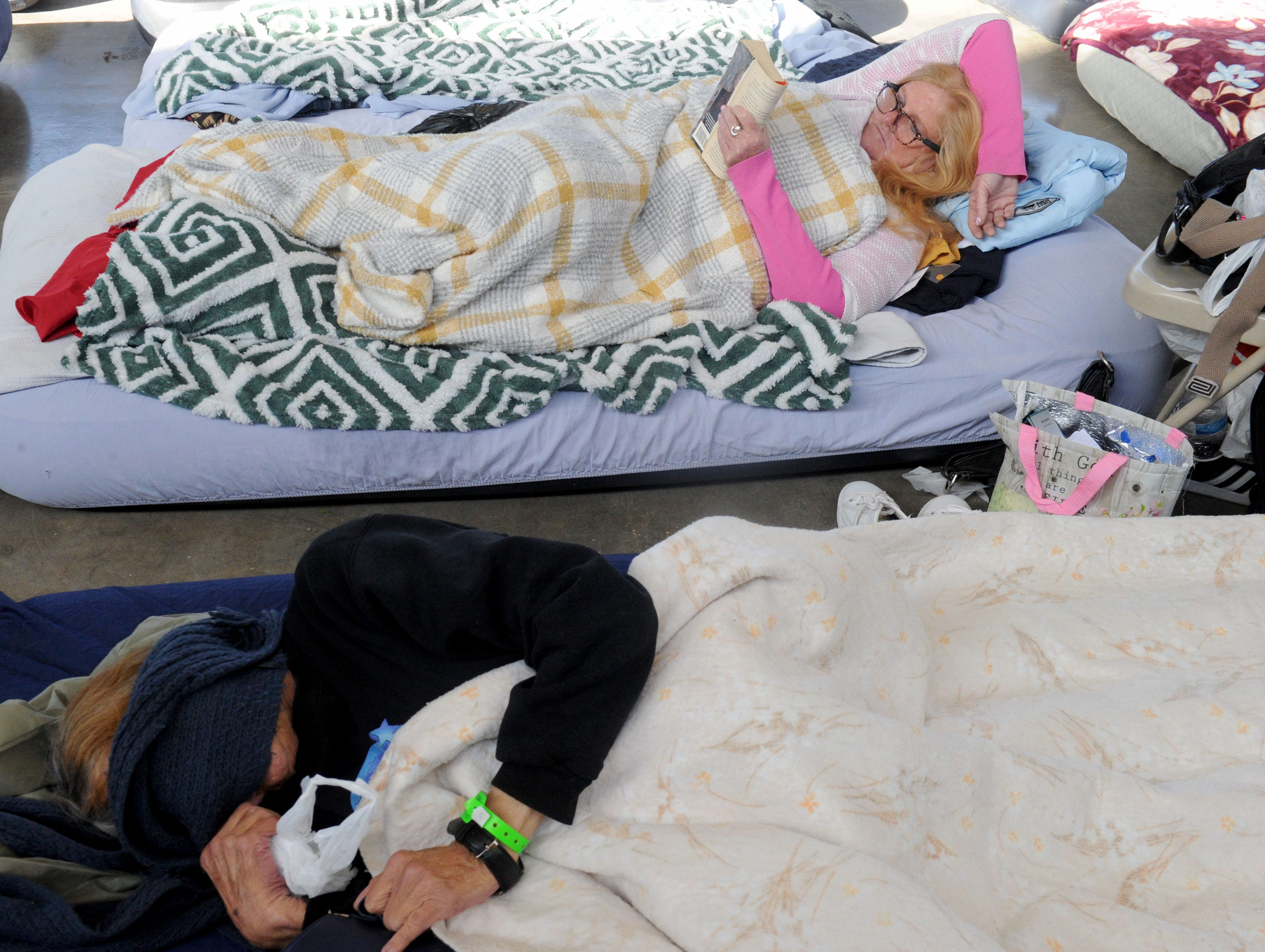 Lila Ashmore reads a book while in bed at the Oxnard homeless shelter.