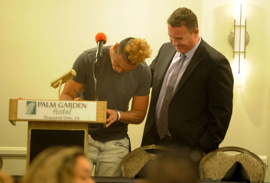 Westlake High's Kamren Fabiculanan signs his name while head coach Tim Kirksey looks on during the Ventura County coaches' annual signing day banquet at the Palm Garden Hotel in Newbury Park on Wednesday. Fabiculanan will play at the University of Washington.