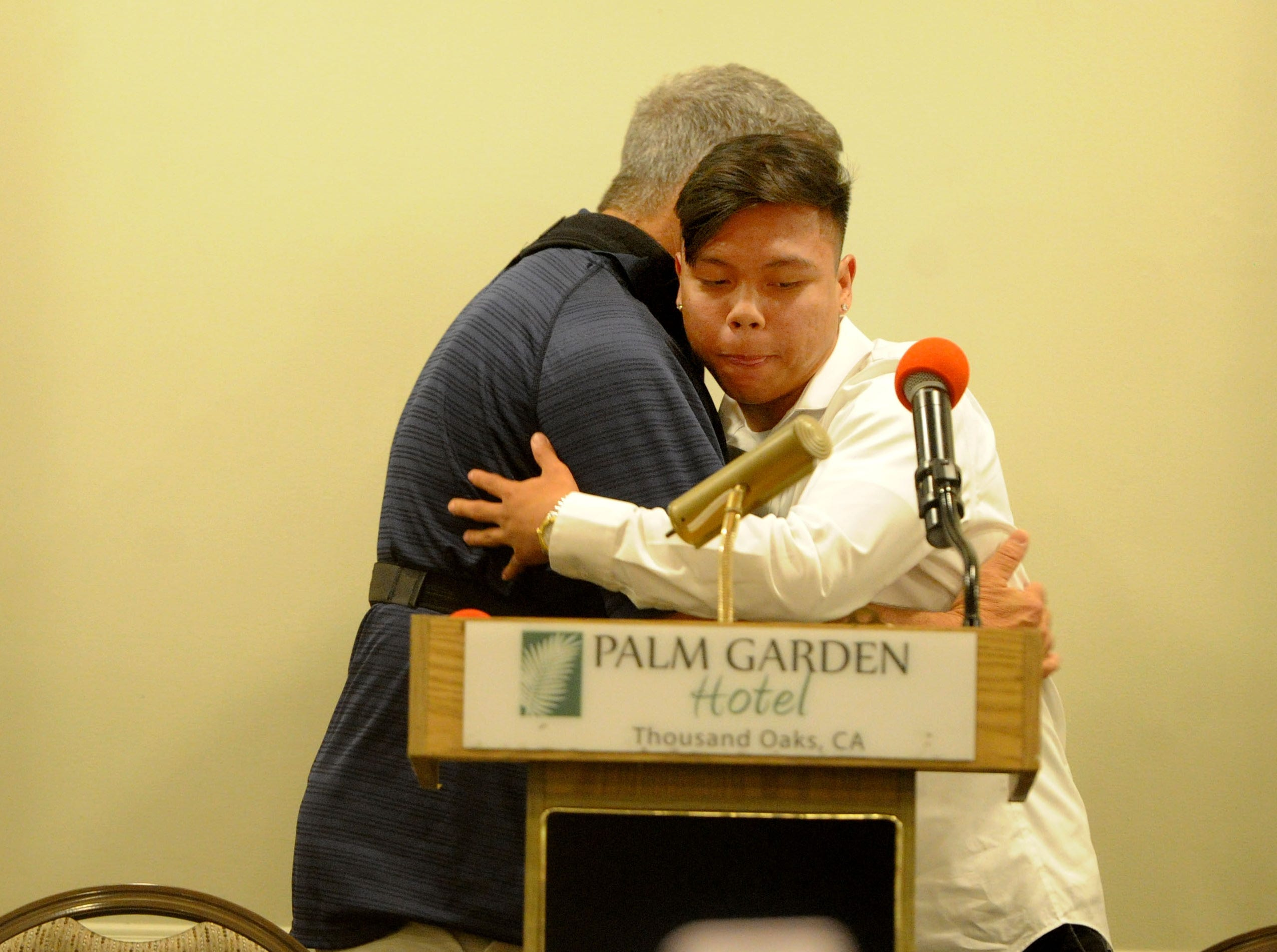 Camarillo High head coach Jack Willard, left, hugs Izaiah Lazaro during the Ventura County coaches' annual signing day banquet at the Palm Garden Hotel in Newbury Park on Wednesday. Lazaro will play at Whittier College.