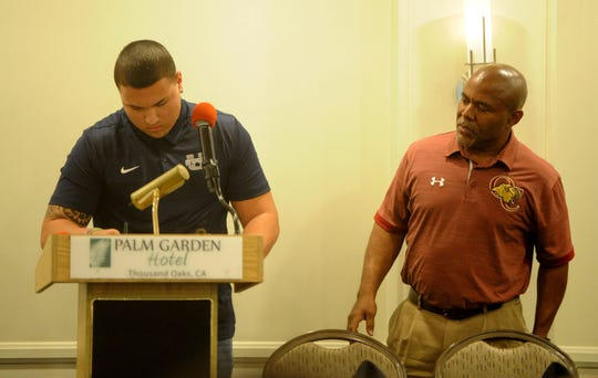 Oaks Christian long snapper Jesse Vasquez signs his name while head coach Charles Collins looks on during the Ventura County coaches' annual signing day banquet at the Palm Garden Hotel in Newbury Park on Wednesday.  Vasquez earned a scholarship to Utah State.