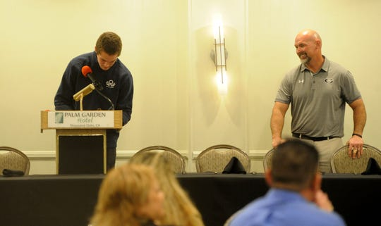 Grace Brethren Justin Skidmore signs him name as head coach Josh Henderson looks on during the Ventura County coaches' annual signing day banquet at the Palm Garden Hotel in Newbury Park on Wednesday. Skidmore will play at Azusa Pacific University.