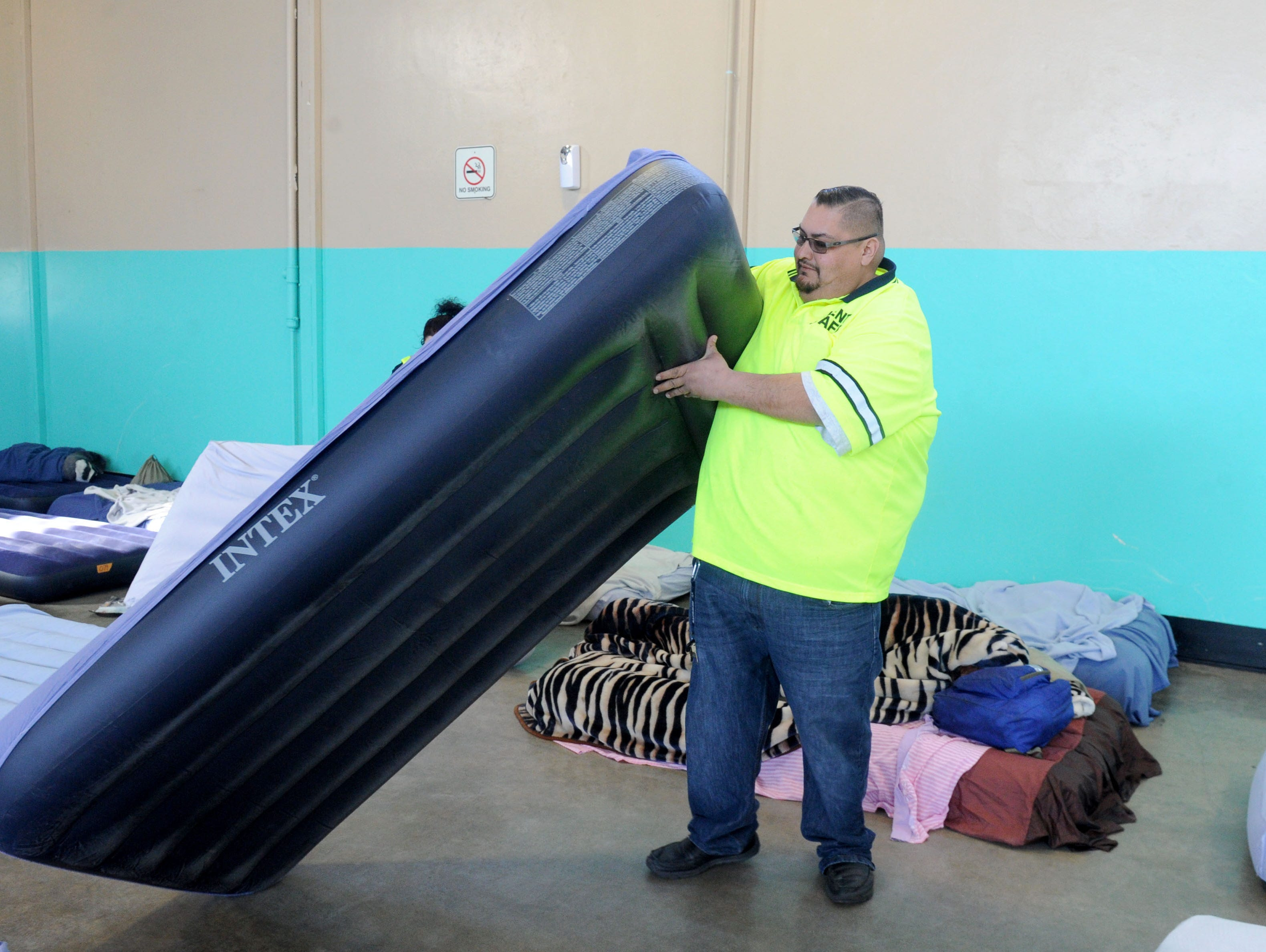 Pancho Vega, a worker at the Oxnard homeless shelter, moves an inflatable bed.