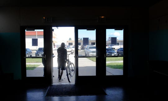 Samuel Foster leaves the Oxnard homeless shelter with his bicycle to run errands.