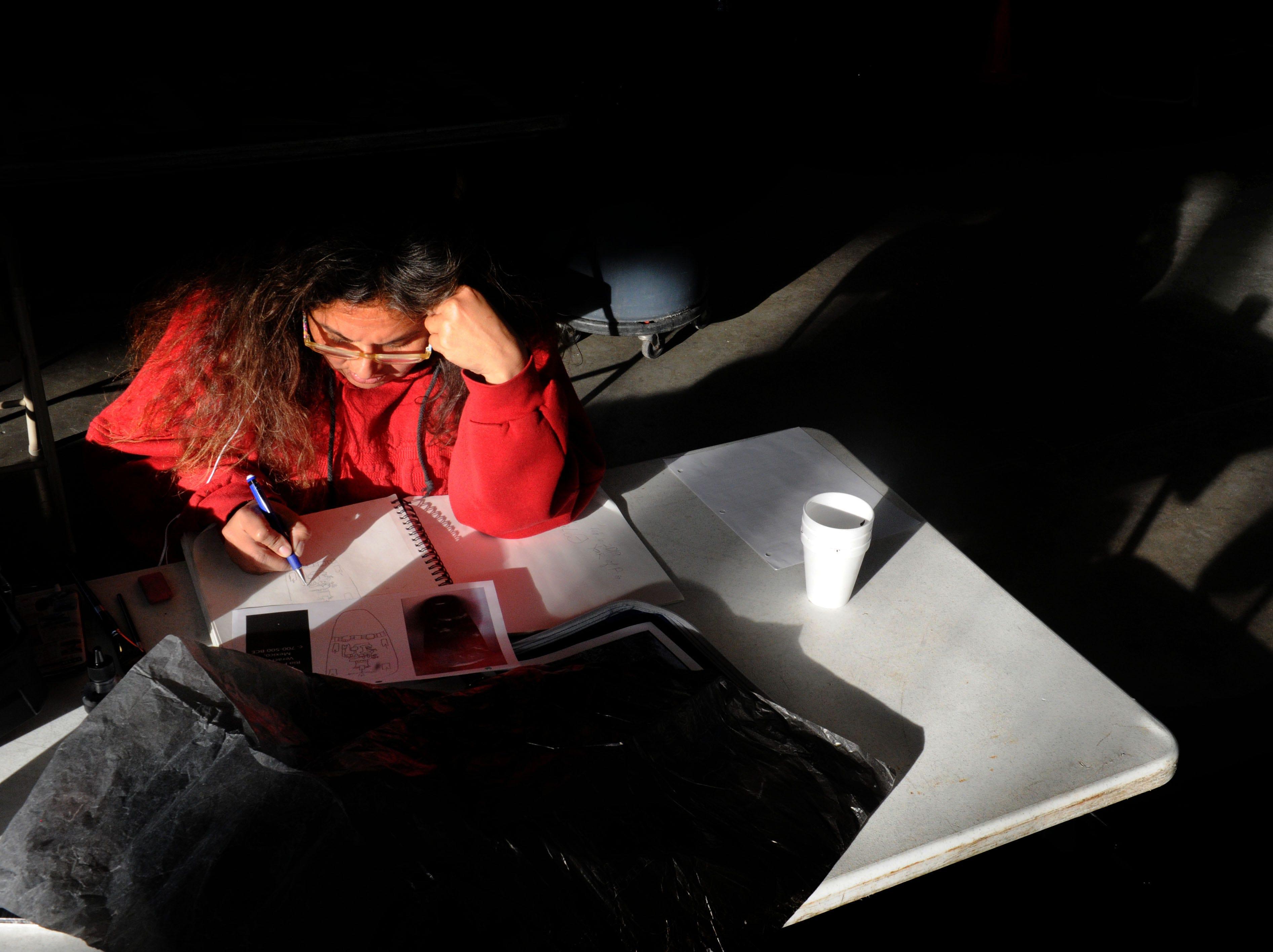 Noe Estrella works on her homework at the Oxnard homeless shelter.