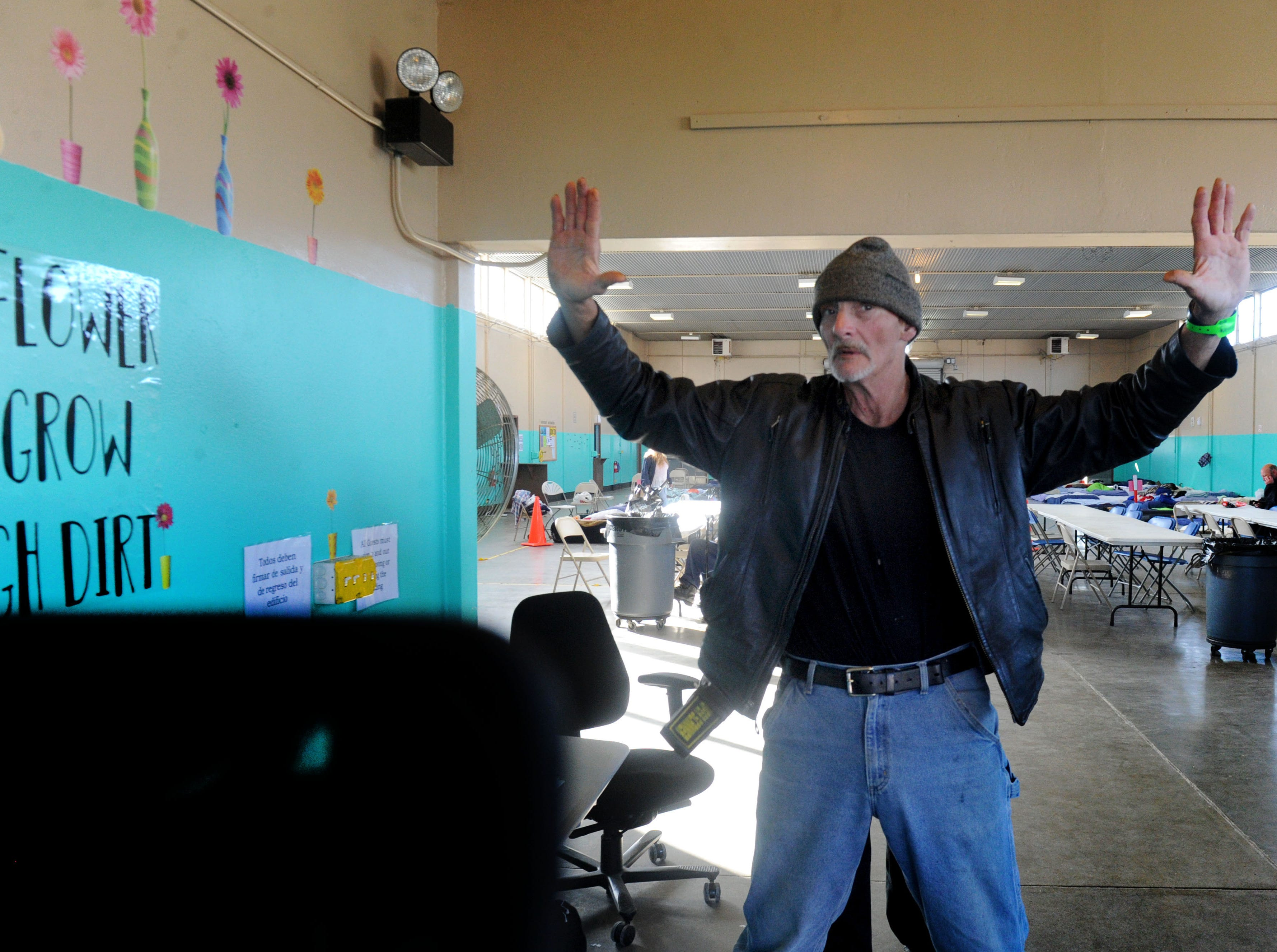 Scott Stebbings gets checked by security guard Steve Pena before entering the Oxnard homeless shelter.