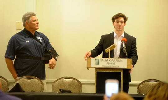 Camarillo High's Jack Holden speaks as head coach jack Willard looks on during the Ventura County coaches' annual signing day banquet at the Palm Garden Hotel in Newbury Park on Wednesday. Holden is headed to Claremont McKenna College.