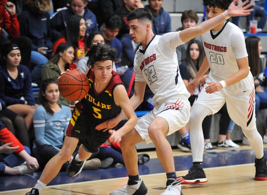 Tulare Union's Aaron Bales dribbles around Tulare Western's Jose Valencia during the Tulare Western against Tulare Union match East Yosemite League Central Section match at Tulare Western on Feb 2, 2019.
