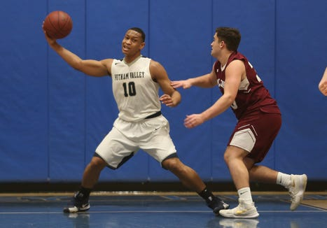 Putnam Valley's Darnel Shillingford (10) pulls down a rebound in front of Albertus Magnus' Steven Travaglini (33) during basketball action at Putnam Valley High School Feb. 5,  2019. Putnam Valley won the game 46-45.