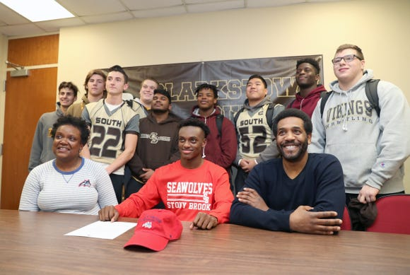 Surounded by teammates, Clarkstown South's RJ Lamarre, center, with his mother Daphnee Momperousse, left, and uncle Will Figaro, signs to play football for Stony Brook at Clarkstown High School South in West Nyack on Wednesday, February 6, 2019.