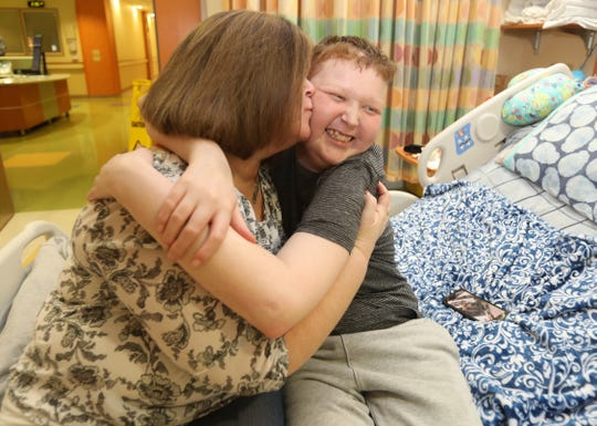Zachary Losee, a heart transplant recipient gets a kiss from his mom, Julie Prest in his room at Blythedale Children's Hospital Feb. 5, 2019.  Zach wants to become an organ donor advocate after getting a new heart.