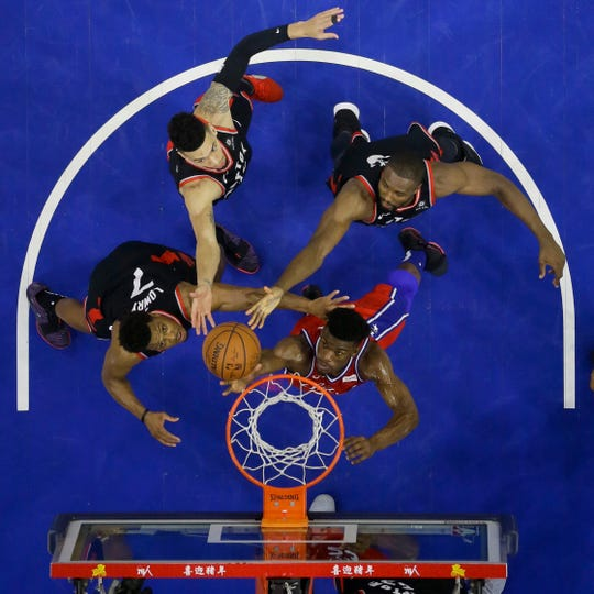 Philadelphia 76ers' Jimmy Butler, bottom right, battles for a rebound with Toronto Raptors' Kyle Lowry, from left, Danny Green and Serge Ibaka during the first half of an NBA basketball game, Tuesday, Feb. 5, 2019, in Philadelphia. (AP Photo/Matt Slocum)