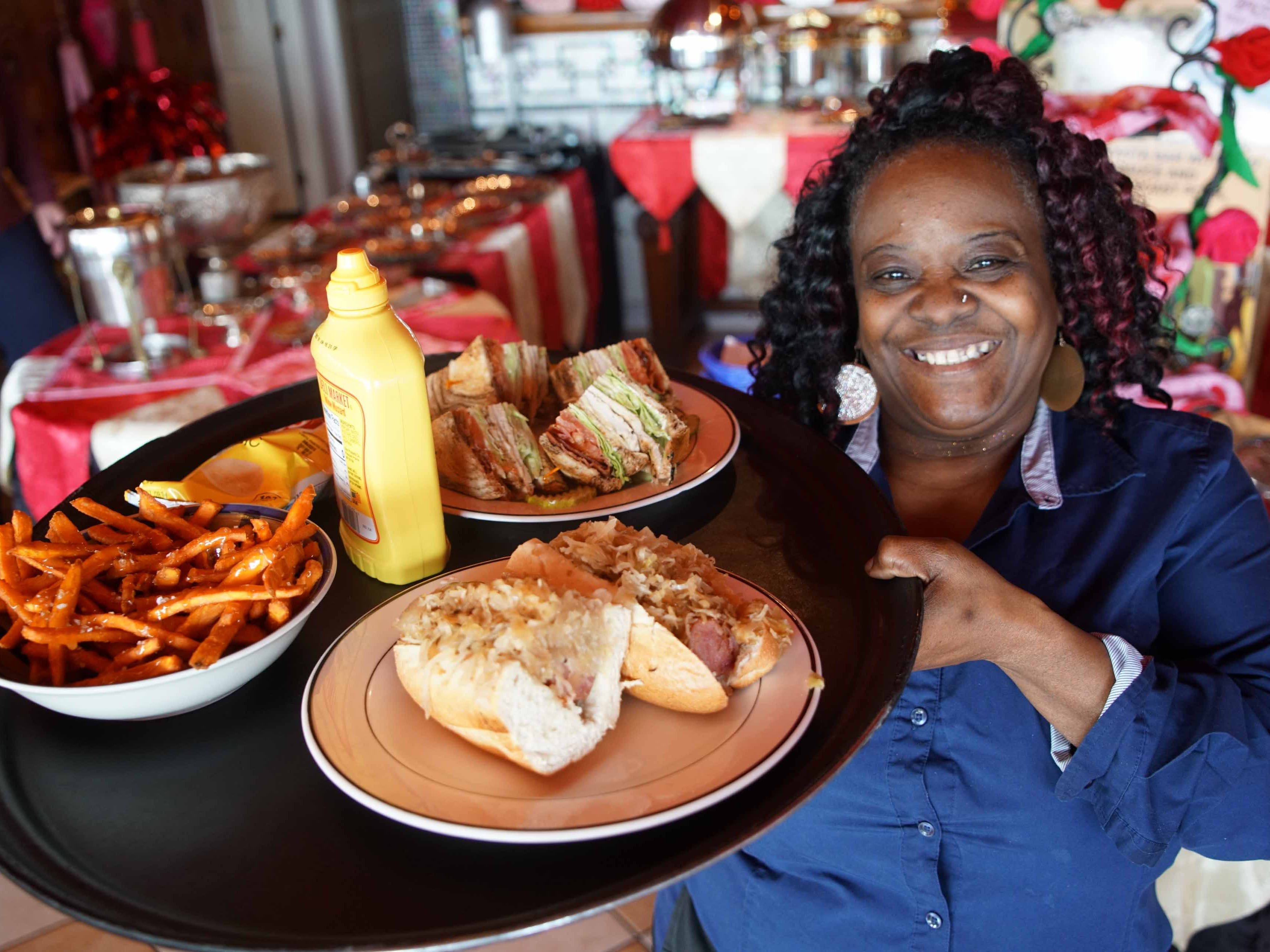 Sheila Loper, a server at Serendipity Restaurant in Oak Orchard, holds a tray of food for patrons visiting the establishment located on Indian River.