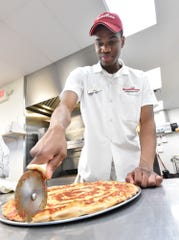 A pizza supervisor cuts a freshly baked pizza at Milford's Grotto Pizza. The Rehoboth Beach-born chain will celebrate its 60th anniversary next year.