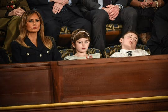 First lady Melania Trump (L) with Grace Eline and Joshua Trump, special guests of President Donald Trump, look during of the State of the Union address at the US Capitol on February 5, 2019 in Washington, DC.