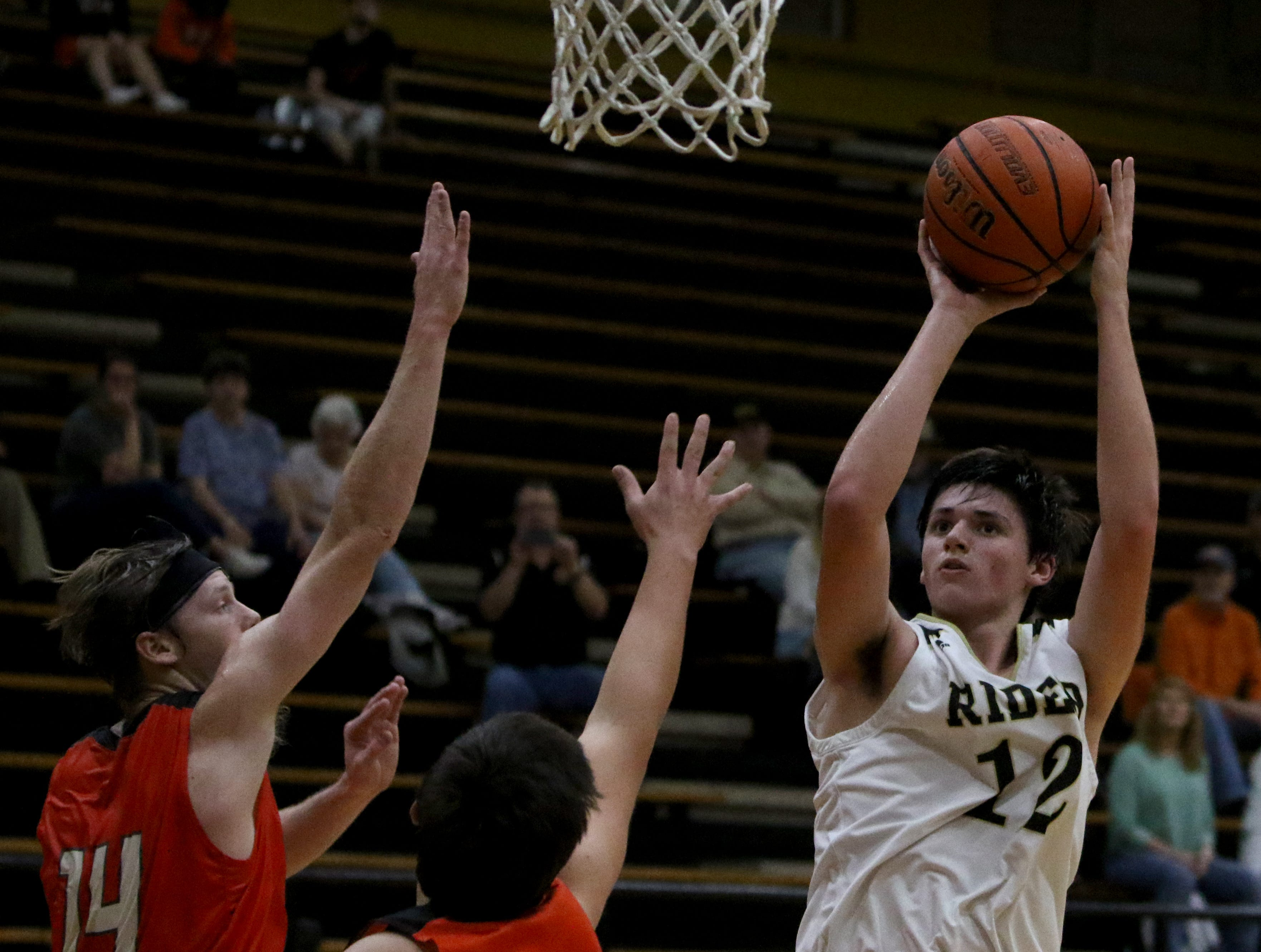 Rider's Ty Caswell shoots over Aledo defenders Tuesday, Feb. 5, 2019, at Rider. The Raiders defeated the Bearcats 64-51.