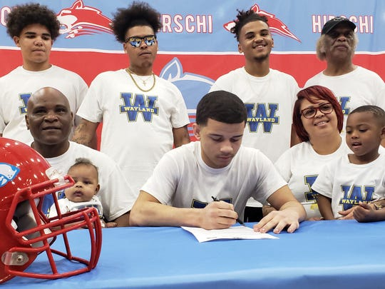 Hirschi senior JaRon Humphrey (sitting center) signed a letter of intent to play football at Wayland Baptist University on Wednesday.