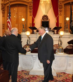 Adam Holmes shakes hands with Larry Household on Wednesday. Holmes was sworn in as representative for the 97th District, which encompasses Guernsey County and the majority of Muskingum County.