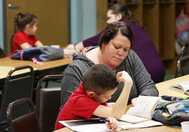 Bradley Harney, 9, reads with Dessi Craig, Youth Manager at Eastside Community Ministries, during Eastside's after school program on Wednesday. The program is one of the beneficiaries of Eastside's annual chair auction.