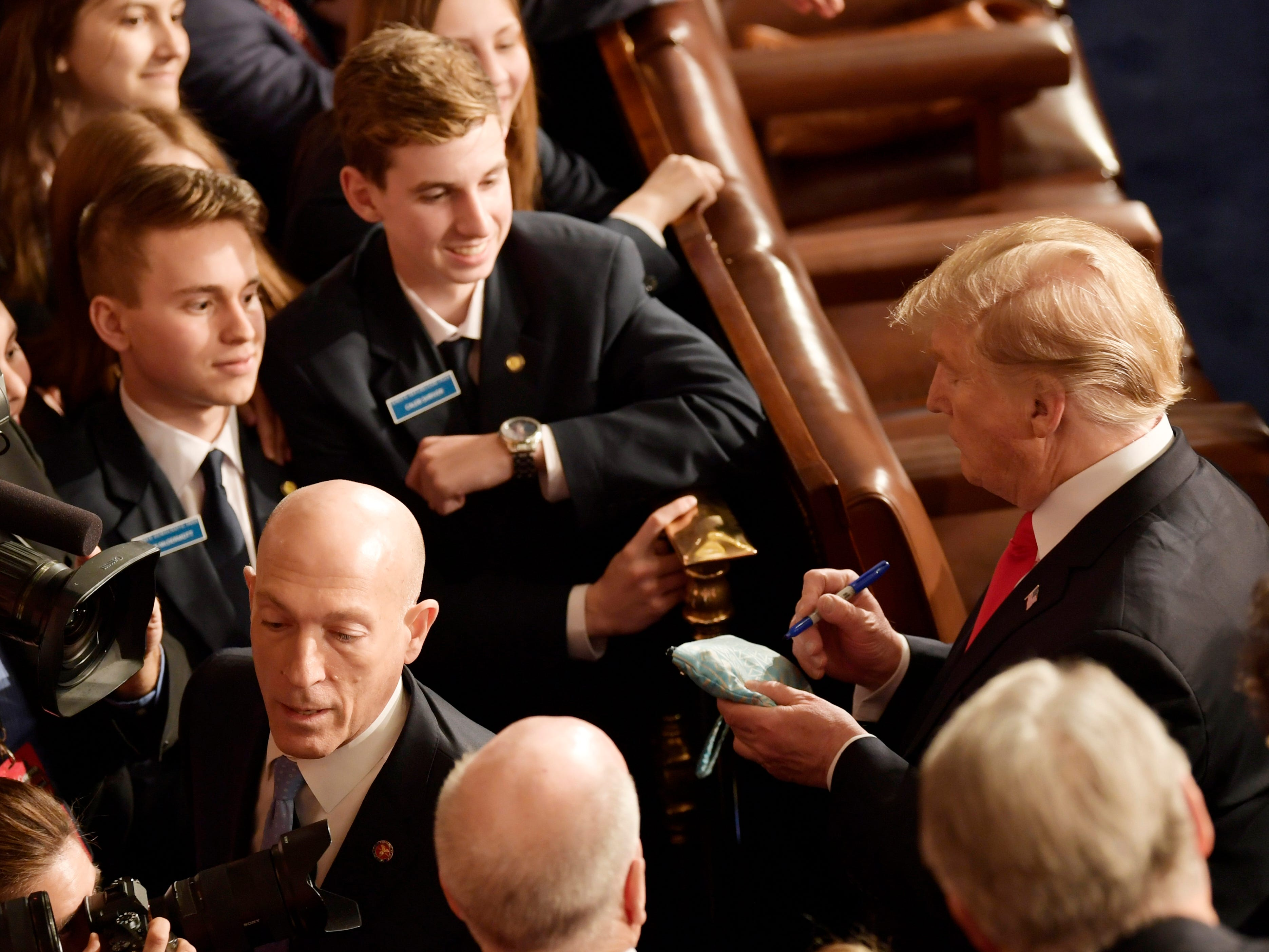 President Donald Trump signs an autograph after delivering the State of the Union address.